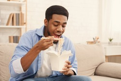 Hungry african american guy eating noodles, enjoying asian food delivery service, free space