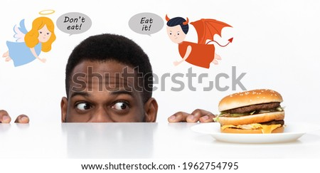 Hungry African American guy looking at unhealthy burger on table, craving to eat it, being tempted by devil and angel, having difficulty making decision on white studio background, panorama. Collage Stockfoto ©