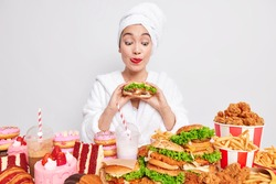 Hungry Asian woman licks red painted lips looks at tasty hamburger picks delicious snack break diet wears bathrobe and towel on head after taking shower chooses from yummy appetising fast food
