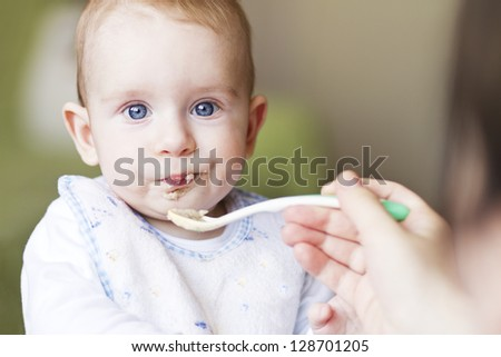 Hungry baby boy with blue eyes eating porridge