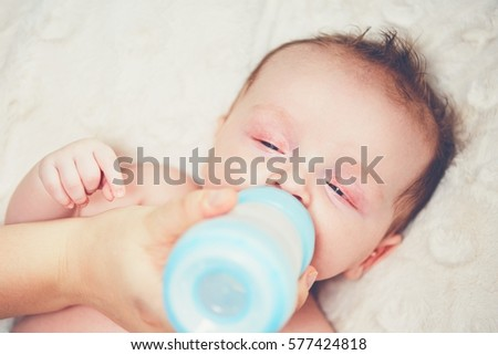 Hungry baby drinking milk. Mother feeding her little boy from bottle.
