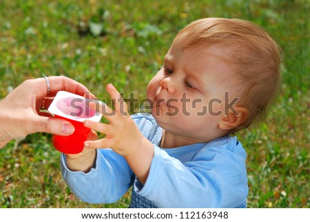 hungry baby girl taking yogurt from mother`s hand outdoor (focus on face)