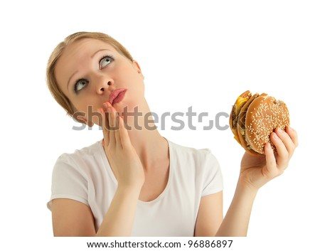 hungry beautiful girl eats a tasty hamburger an isolated on white background