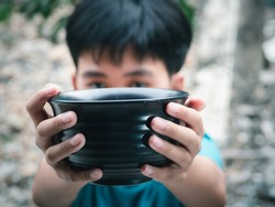 Hungry boy holding empty black bowl waiting for food for sustenance with unhappy. Asking help food donation from traveler on street at the city. Unidentified homeless child begging on street.
