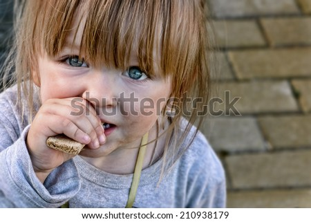 Hungry caucasian child with big clear eyes eating bread and impressively looking at the camera. Close-Up.