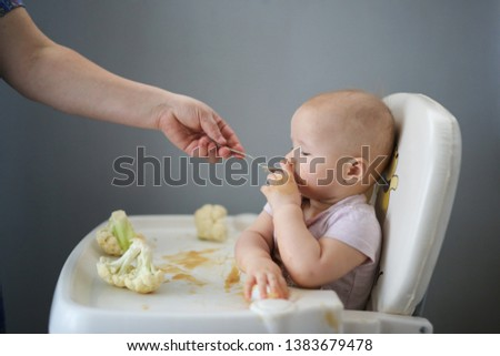 Hungry charming baby eats a vegetable puree with a spoon, close-up on a gray background, funny grimy baby, 10 months old, eats cauliflower puree