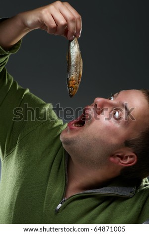 Hungry corpulent man with open mouth staring at a fish