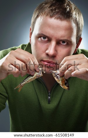 Hungry corpulent man with two halfs of fish in hands