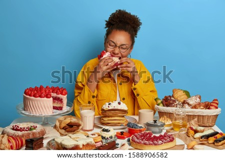 Hungry curly African American woman bites big piece of cake, feels temptation after diet, sits at table overloaded with sweet dishes, loves desserts, being sweettooth or glutton, poses indoor Stock photo ©