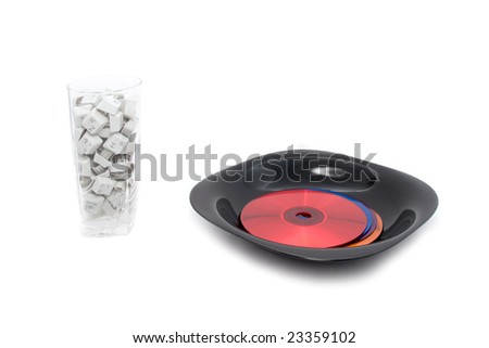 Hungry for information: multicolor dvd disks on dinner plate, keyboard keys in glass