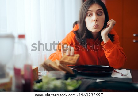Hungry Girl Eating Bread Slice Before Dinner. Gluttonous impatient person eating the toast before the meal arrives  Stock photo ©