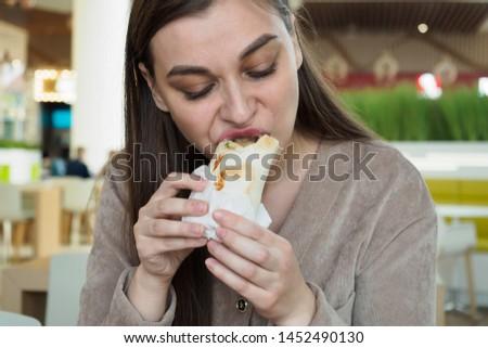Hungry girl eating shawarma, enjoying delicious but unhealthy food #1452490130