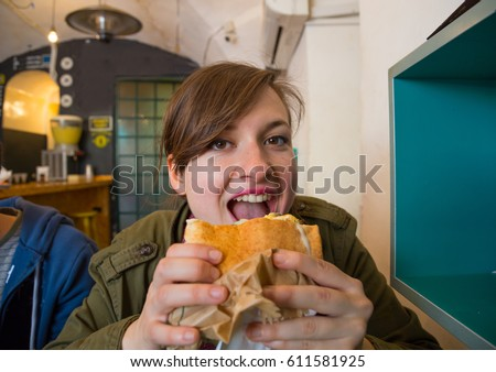 Hungry handsome woman is biting sabih sandwich looking at the camera. Sabih is an Jewish- Iraqi and Israeli sandwich, consisting of pita stuffed with fried eggplant and hard boiled eggs. #611581925