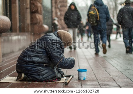 Hungry homeless beggar woman beg for money on the urban street in the city from people walking by Foto d'archivio ©