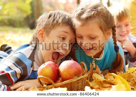 Hungry kids biting autumnal apples