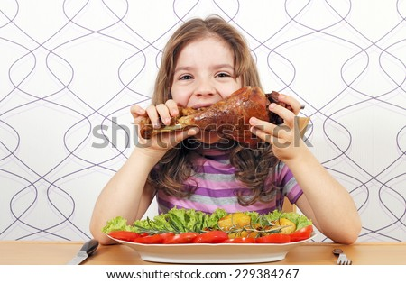 hungry little girl eating big turkey drumstick