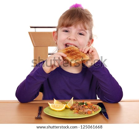 hungry little girl eating bread