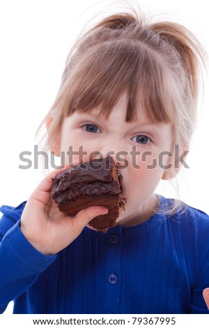 Hungry little girl eating chocolate cake looking at camera
