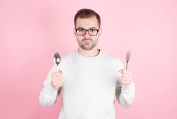 Hungry man holds a fork and spoon in his hands and thinks about delicious food over pink background . Diet and meal concept.