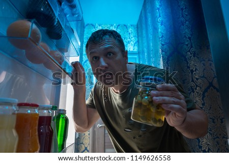 Hungry man searching in his fridge at night for a snack holding a jar of pickles as he peers inside viewed from inside the refrigerator looking out through the open door #1149626558