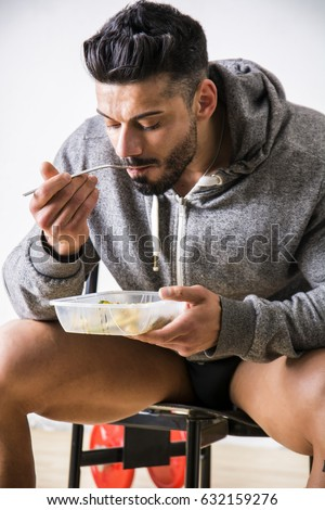 Hungry muscular young man gulping down food looking at plastic container without pausing as he takes another mouthful