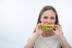 Hungry pretty woman is biting hamburger gradually. She is looking at the camera malevolently. Isolated on a white background. There is copy space in the left side