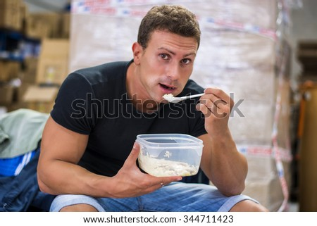 Hungry shirtless muscular young man gulping down food glancing across at the camera without pausing as he takes another mouthful