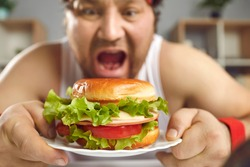 Hungry sportsman who failed his diet eating fattening junk food. Man enjoying delicious high-fat burger with cheese, tomato and fresh lettuce. Close up funny guy putting big cheeseburger in open mouth