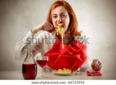 Hungry woman eating pasta and drinking red wine - stock photo
