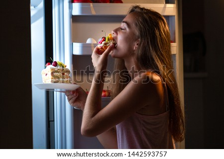 Hungry woman in pajamas eating sweet cakes at night near refrigerator. Stop diet and gain extra pounds due to high carbs food and unhealthy night eating
