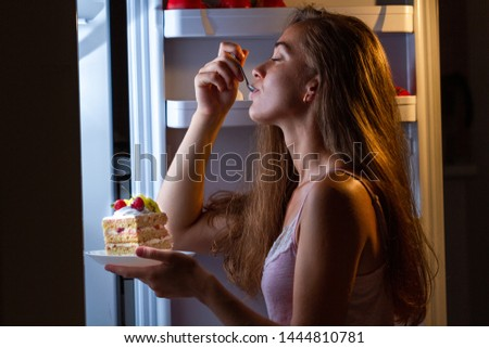 Hungry woman in pajamas enjoys sweet cake at night near refrigerator. Stop diet and gain extra pounds due to carbs food and unhealthy eating  #1444810781