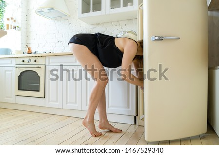 Hungry Woman looking for food in white retro refrigerator in modern bright apartments. Diet keeping concept. Loosing weight or gaining muscles. Evening hunger. Preparing breakfast.