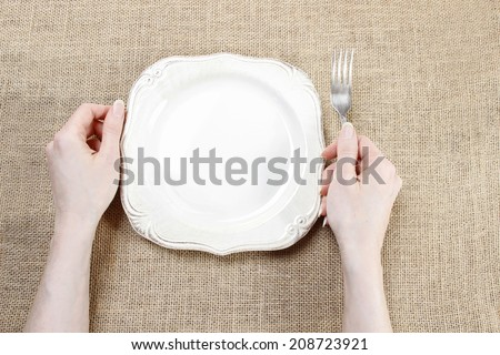 Hungry woman waiting for her meal over empty plate.