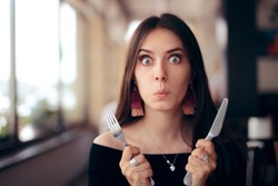 Hungry Woman with Knife and Fork Ready to Eat. Greedy impatient girl waiting for her dish in a restaurant