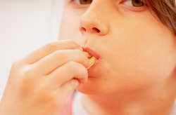 Hungry young beautiful girl eating french fries and puts potatoes in her mouth. Selective focus on french fries. Unhealthy fast food and calorie food.