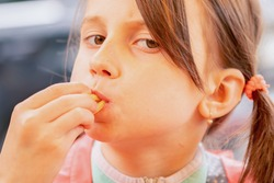Hungry young beautiful girl eating french fries and puts potatoes in her mouth. Unhealthy fast food and calorie food.