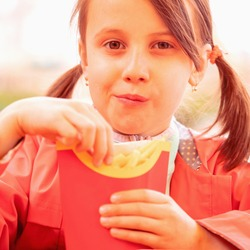 Hungry young beautiful girl puts potatoes in her mouth. Unhealthy fast food and calorie food.