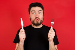 hungry Young caucasian man wearing black t-shirt over red background holding in hand fork knife want tasty yummy pizza pie