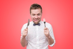 Hungry young man holding fork and knife on hand ready to eat, licking lips. Diet and healthy food concept.