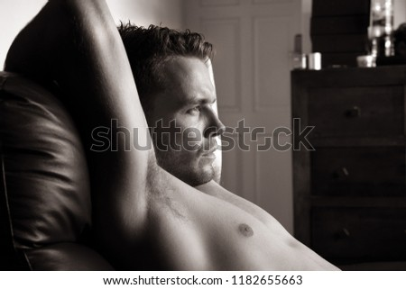 Hunky handsome shirtless man with pecs, abs and muscles looking out of window #1182655663