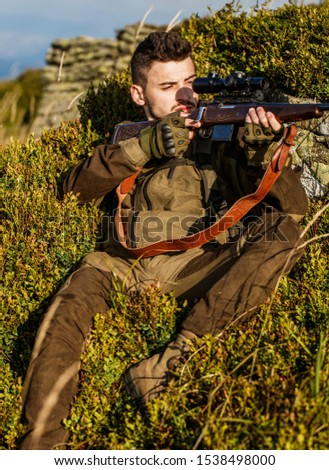 Hunt hunting rifle. Hunter man. Hunting period. Male with a gun. Close up. Hunter with hunting gun and hunting form to hunt. Hunter is aiming. Shooter sighting in the target. The man is on the hunt.