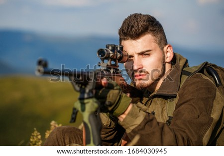 Hunt hunting rifle. Hunter man. Shooter sighting in the target. Hunting period. Male with a gun. Close up. Hunter with hunting gun and hunting form to hunt. Hunter is aiming. The man is on the hunt.