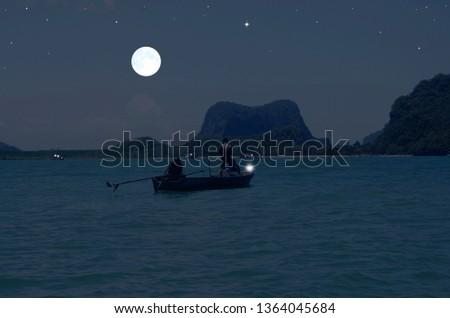 Hunter fishermen in boat under full moon light