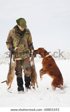 Hunter getting the hare from the dog during a winter hunting party