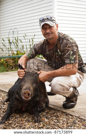 Hunter holding killed wild boar up for picture
