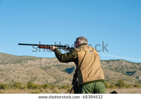 Hunter in action aiming and shooting his rifle