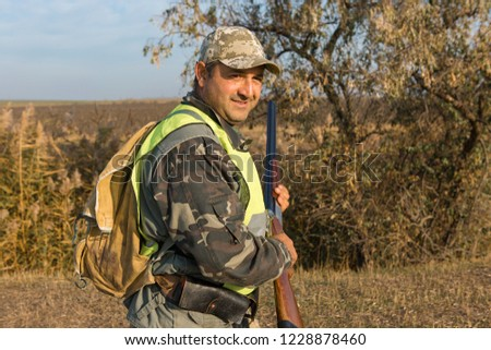 Hunter in camouflage and with a gun #1228878460