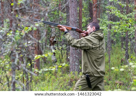 Hunter in camouflage ready to hunt with hunting shotgun. Aiming for prey #1461323042