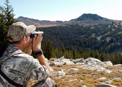 Hunter in camouflage using binoculars to search Montana hills for animals