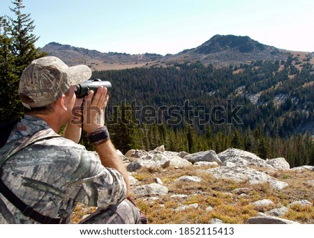 Hunter in camouflage using binoculars to search Montana hills for animals Foto d'archivio ©